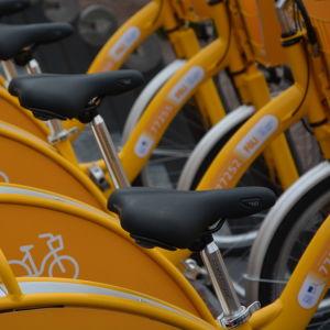 Närbild på sadlar på gula stadscyklar i Åbo.