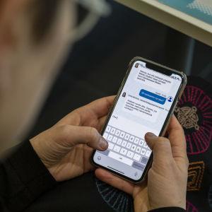 Person håller en mobiltelefon med båda händerna och skriver i en chat.