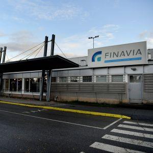 Karleby-Jakobstad flygplats. Utanför flygplatsen står en röd paketbil parkerad.