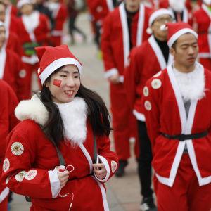Invånare i Peking utklädda till julgubben värmer upp för Santa Claus fun run (ungefär julgubbsloppet). Bilden från 22 december 2018.