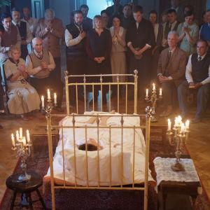 Maria Åkerblom (Pihla Viitala) ligger i en säng omringad av levande ljus och anhängare som ivrigt väntar på hennes predikan.
