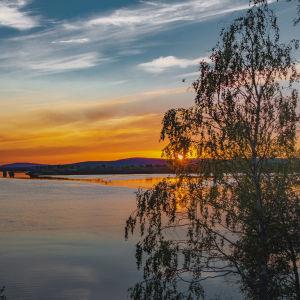 Keskikesän yötön yö Rovaniemellä, maisema Lainaalta joelle kohti nelostien siltaa.