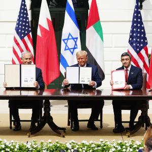 Vasemmalta Bahrainin ulkoministeri, Israelin pääministeri, Yhdysvaltain presidentti ja Arabiemiraattien ulkoministeri istuvat pöydän takana näyttäen yleisölle allekirjoitettuja sopimuksia, taustalla valtioiden lippuja