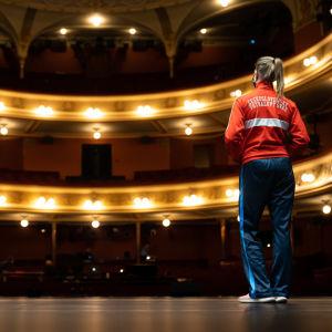 Auri Ahola fotograferad bakifrån på scenen i Nationalteatern framför tomma läktare..