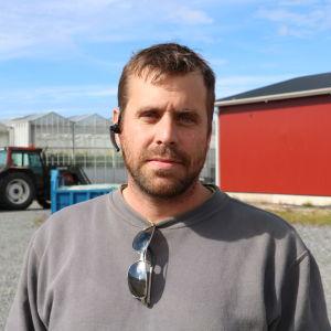 En man med kort brunt hår och skägg står framför ett stort växthus. I bakgrunden syns också en traktor med släp.