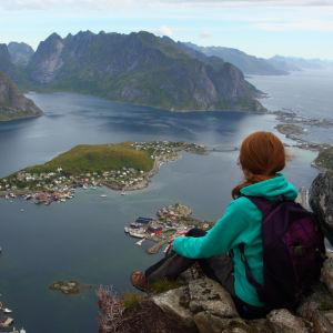 Person sitter och ser ut över en fjord