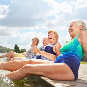 Tre äldre kvinnor och en man sitter på en brygga och plaskar med fötterna i vattnet