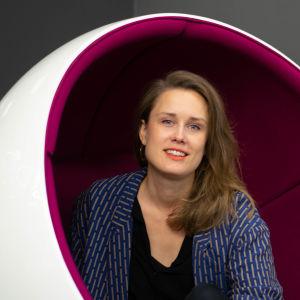 Eva-Maria Koskinen poserar i rund bollstol i Yles aula.