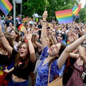 Valtava ihmisjoukko sateenkaariliput käsissään.