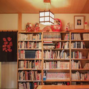 Kirjahylly, päällä Japanin ja Suomen pöytäliput, japanilainen valaisin, tekstiilejä