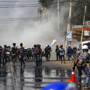 Poliisi suihkuttaa kyynelkaasua mielenosoittajia päin Mandalayn kaupungin kadulla.