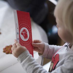 ett barn håller i ett gåvokort