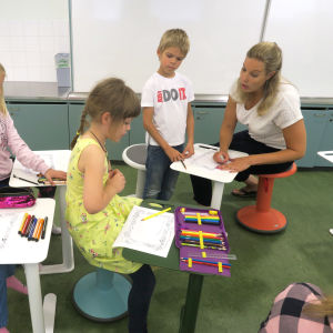 Opettaja neuvoo oppilaita luokassa.