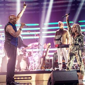 Kaksi henkilöä laulaa ja molempien käsi osoittaa ylöspäin. Taustalla bändi.