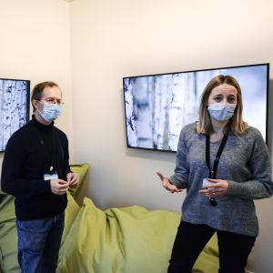 En man och en kvinna i munskydd står inne i ett rum och berättar något mot kameran. I bakgrunden syns stora gröna kuddar och två skärmar på väggen som visar naturbilder.