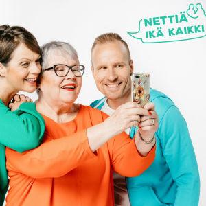 Nettiä ikä kaikki -kampanjan kärkihahmot Anna-Liisa Tilus ja Mikko Kekäläinen katsovat älypuhelimen ruutua yhdessä eläkeikäisen naisen kanssa. Kuvassa on teksti Nettiä ikä kaikki.