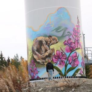 En kvinna med mörk jacka står framför en väggmålning på ett vindkraftverk.