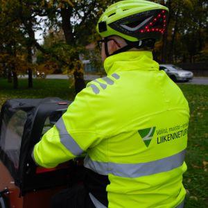 Trafikskyddets sambandschef Elias Ruuti cyklar med en lådcykel på en cykelväg iklädd varnigskläder.