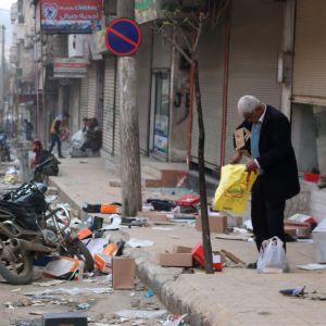 En man utanför en butik som utsatts för plundring i Afrin.