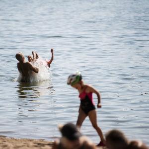 Folk badar vid stranden i Helsingfors.