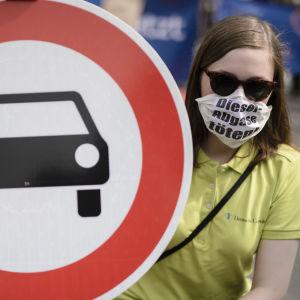 En demonstrant med ansiktsmask håller upp en förbudsskylt mot bilar.