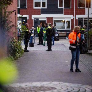I förgrunden ser man en kvinna i reflexväst som kollar på någonting hon har i handen, i bakgrunden står poliser och väntar på någonting