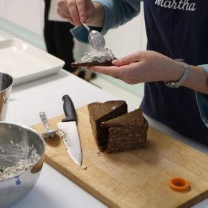 En person håller på att bre svampsallad på triangulära brödskivor.