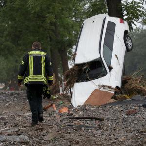 En brandman rör sig i Bad Neuenahr-Ahrweiler efter översvämningar. En bil har välts omkull.