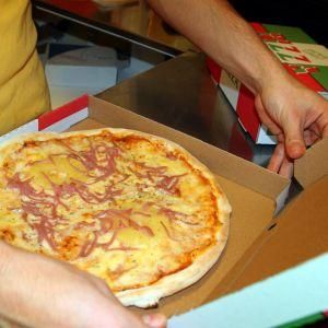 Man sätter pizza i kartonglåda