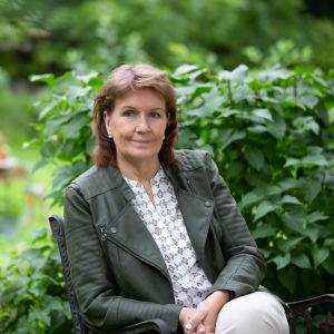 Författare Benita Backas-Andersson sitter i trädgård