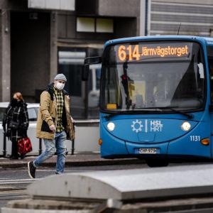 Gatuvy med en blå buss och några fotgängare som bär munskydd. Vy från Berghäll i Helsingfors den 16 mars.