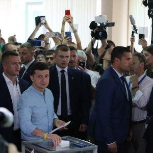 Ukrainan presidentti Volodymyr Zelenskyi poseeraa lehdistölle ja pitelee äänestyslipuketta laatikon suuaukolla ja kansanedustaja Ilkka Kanerva katselee vieressä.