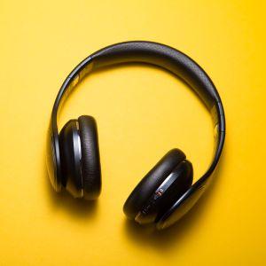Ett par hörlurar på gul bakgrund.
