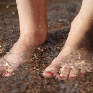 Fötter med lackade naglar i vatten
