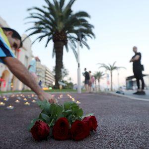 Man lägger ner vid rosor vid Promenade des Anglais i Nice den 14 juli 2017, där en förödande terrorattacken skedde ett år tidigare.