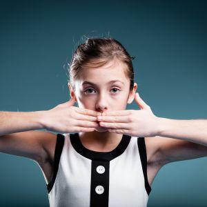 En flicka håller händerna framför sin mun.
