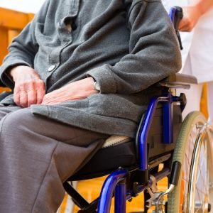 Äldre person sitter i en rullstol som en vårdare skuffar fram.