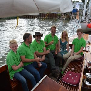 Sex besättningsmän avnjuter champagne i en förtöjd segelbåt.