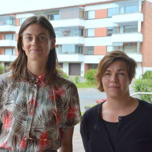 Maria Nilsson Waller och Annika Sillander poserar utanför Yle. I bakgrunden finns ett höghus.