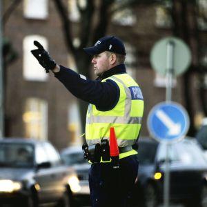 Polis i gul väst dirigerar trafiken.