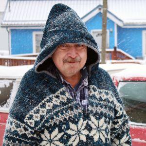 Mies villapaidassa lumisateessa.