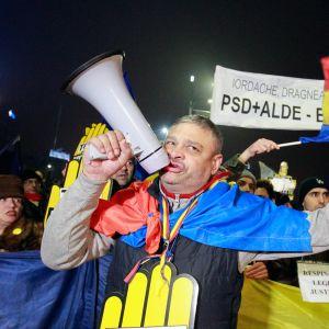 En man ropar slagord i en megafon under demonstrationen utanför regeringspalatset i Bukarest, 26.11.2017.