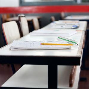 En pulpetrad med häften i ett klassrum.