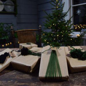 Fem paket dekorerade med grönt garn och tofsar.