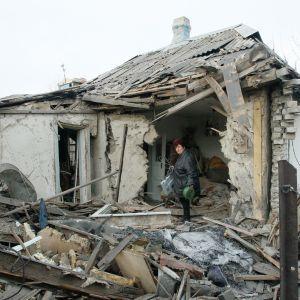 En kvinna hämtar saker ur sitt sönderskjutna hus i byn Jasinovataja i Donetsk-regionen den 21 december. Byn kontrolleras av proryska rebeller.