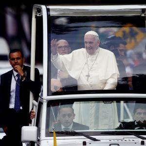 Påve Franciskus vinkar från sin påvemobil efter ankomsten till Santiago.