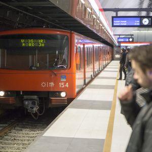 Ihmisiä ja metrojuna Matinkylän metroasemalla.