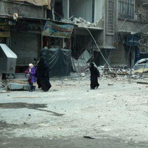 Syriska kvinnor söker skydd då staden Douma i östra Ghouta bombas 10.3.2018.