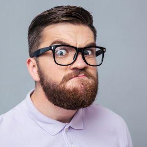 En man med glasögon stirrar surt in i kameran.