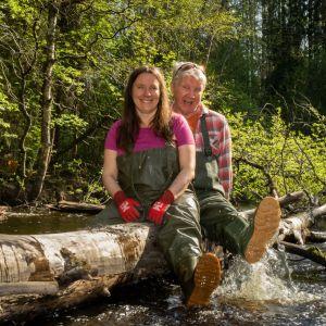 Minna Pyykkö ja Pirkka-Pekka Petelius istuvat puunrungolla joella.
